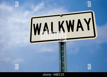A white WALKWAY sign indicating a pedestrian crossing or walking path - Stock Photo