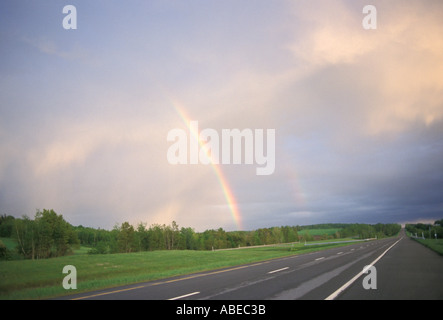 A rainbow with lush green fields and a bare stretch of highway in the foreground  - Stock Photo