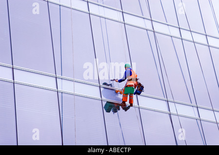 window cleaner suspended on wires at multistorey office block, Glasgow city centre, Scotland - Stock Photo