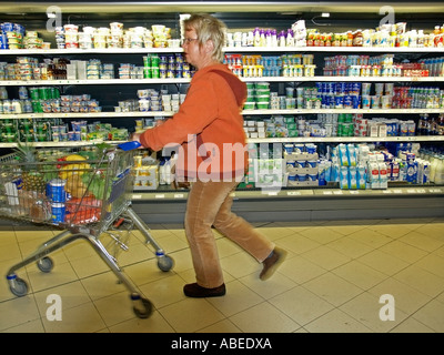 MR woman at the tender age of 40 to 50 years going shopping in a supermarket whoosing busy with a shopping cart - Stock Photo