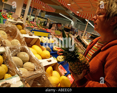 person consumer woman at the tender age of 40 to 50 years shopping in supermarket in department for fruit - Stock Photo