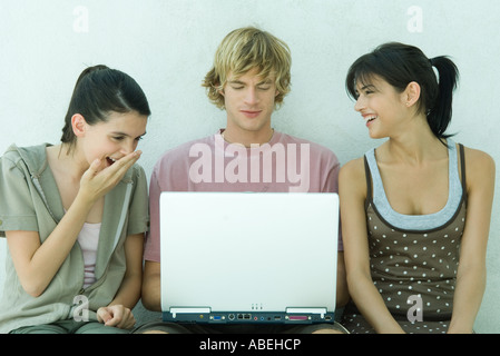 Group of young friends using laptop - Stock Photo