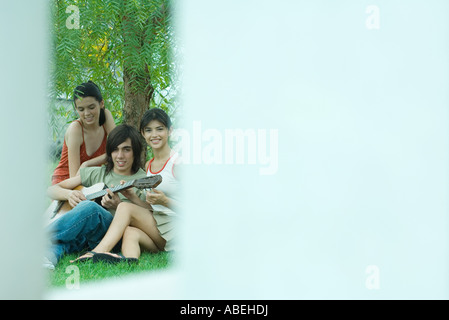 Group of young friends sitting by tree while one plays guitar - Stock Photo