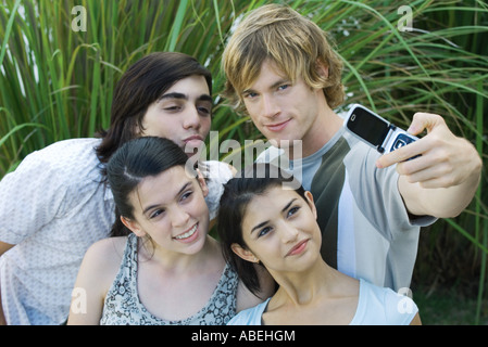 Group of young friends posing while man takes photo with cell phone - Stock Photo