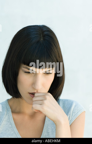Woman biting thumb and looking down, head and shoulders, portrait