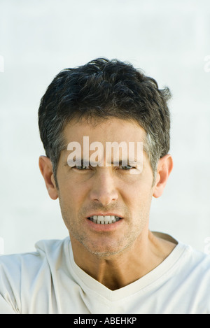 Man scowling at camera, head and shoulders, portrait - Stock Photo