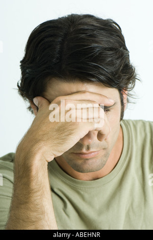 Man, holding forehead, head and shoulders, portrait - Stock Photo