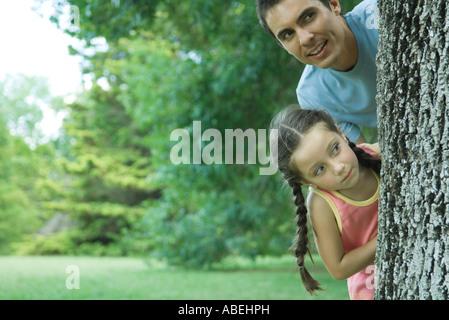Father and daughter peeking around tree trunk - Stock Photo