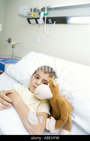 Boy lying in hospital bed next to stuffed animal - Stock Photo