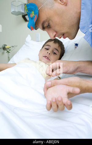 Boy lying in hospital bed, intern wearing mask on head removing adhesive tape from boy's arm - Stock Photo