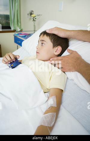 Boy lying in hospital bed having pulse taken - Stock Photo