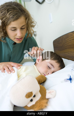 Boy sleeping in hospital bed, intern looking over boy's shoulder - Stock Photo