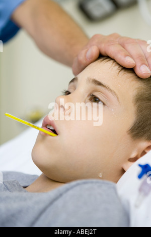 Boy with thermometer in mouth and man's hand on forehead - Stock Photo