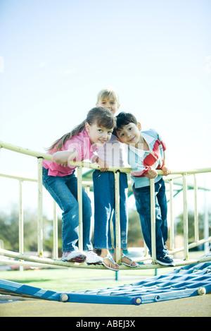 Children on playground equipment, smiling at camera - Stock Photo