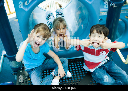 Children on playground equipment, making faces at camera - Stock Photo