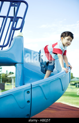 Boy on playground equipment, smiling, looking away - Stock Photo