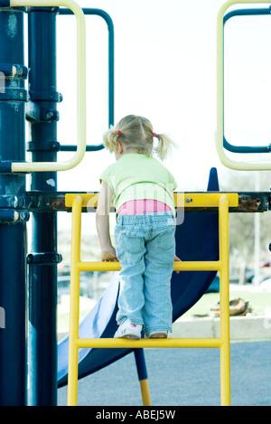 Girl climbing ladder on playground equipment - Stock Photo