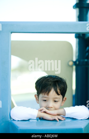 Boy on playground equipment, looking down - Stock Photo