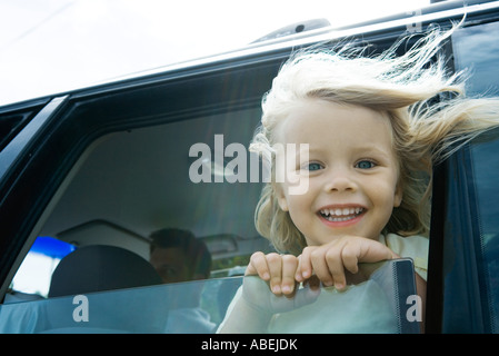 Little girl in car, looking out of window, smiling at camera, hair blowing in wind - Stock Photo