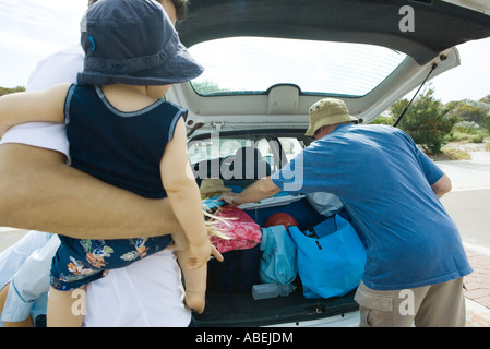 Family unloading beach material out of trunk of car - Stock Photo