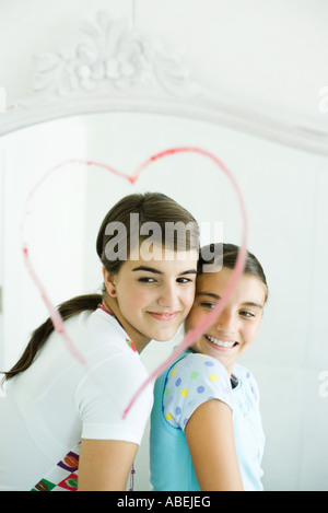 Two young female friends, reflected in mirror with heart drawn in lipstick - Stock Photo