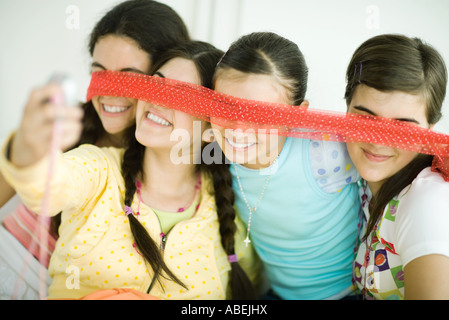 Four young female friends holding scarf in front of eyes, one taking photo with cell phone - Stock Photo