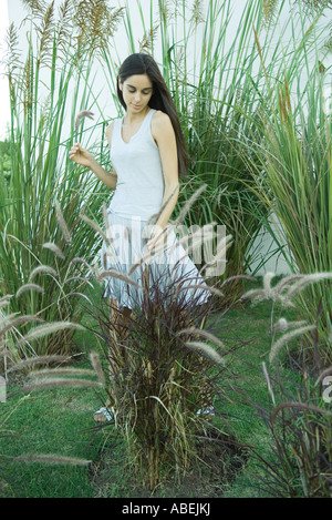 Woman standing among long grasses and reeds, full length - Stock Photo