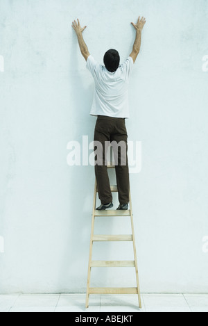 Man standing on ladder, reaching up along wall, full length - Stock Photo