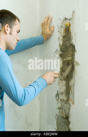 Man filling in hole in wall with grout - Stock Photo