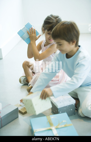 Children sitting on floor picking up presents - Stock Photo