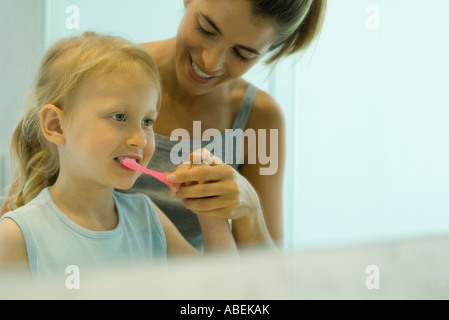 Mother and daughter brushing girl's teeth together - Stock Photo