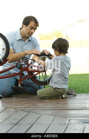 Father and son fixing bike together - Stock Photo