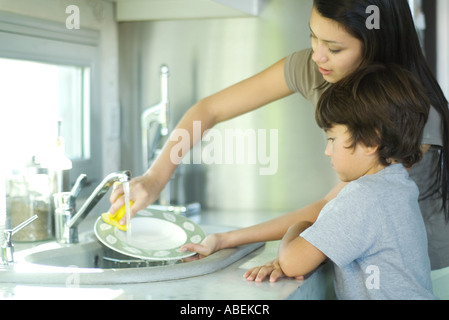 Mother and son washing dishes - Stock Photo