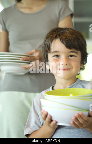 Mother and son carrying dishes together - Stock Photo