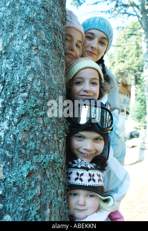 Kids and teens peeking from behind tree in ski clothes, portrait - Stock Photo