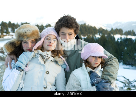 Four young siblings standing in snowy landscape, portrait - Stock Photo