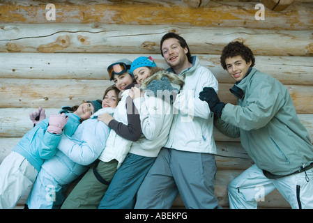 Young friends standing by log cabin, portrait - Stock Photo