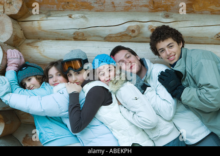 Young friends standing by log cabin, leaning on each other, portrait - Stock Photo