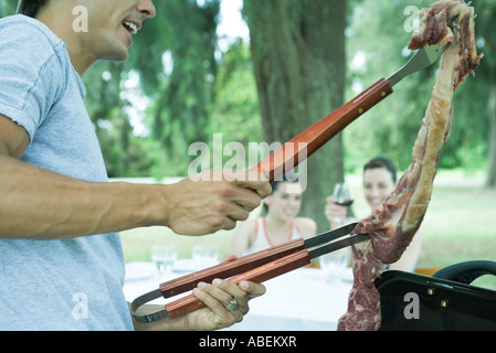 Man holding up piece of meat over barbecue - Stock Photo