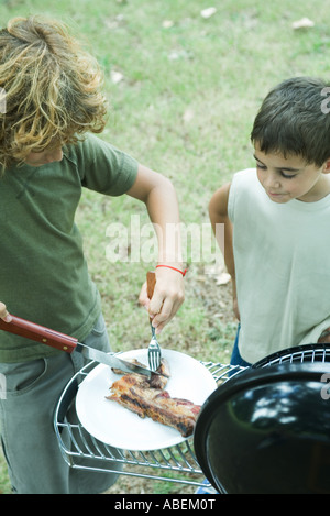 Two boys standing next to barbecue, one cutting up meat on plate - Stock Photo