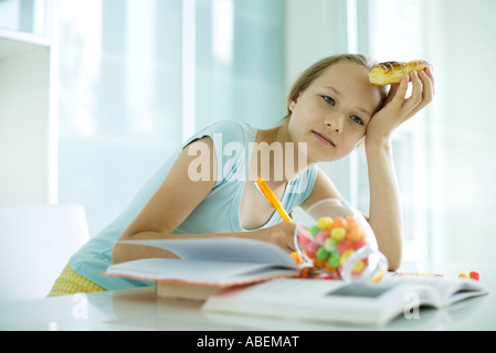 Girl eating sweets and doing homework - Stock Photo