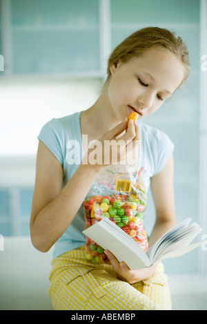 Girl snacking and reading - Stock Photo