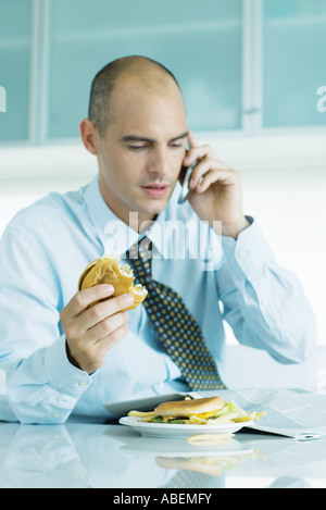Man sitting at table eating hamburgers, reading newspaper and using cell phone - Stock Photo