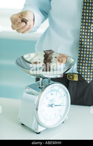 Man stacking chunks of chocolate on kitchen scale - Stock Photo
