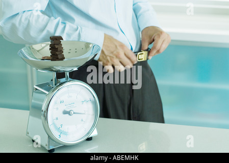 Man standing by scale containing chunks of chocolate on kitchen scale - Stock Photo