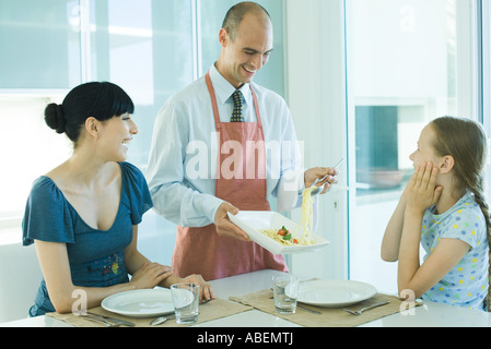 Man serving wife and daughter spaghetti - Stock Photo