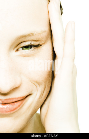 Teenage girl's face, hand on temple, extreme close-up - Stock Photo