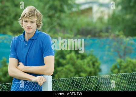 Young man standing next to fence, smiling at camera - Stock Photo