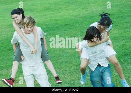 Two young couples, girlfriends being carried piggyback - Stock Photo