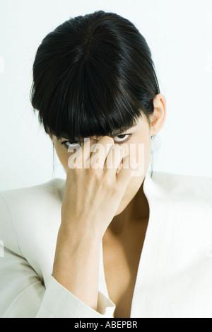 Woman touching bridge of nose, glaring at camera, portrait
